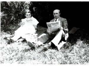 "A couple reads ""Aufbau"" outdoors in the 1950's."