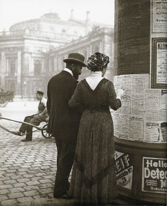 A man and woman view theater listings on an advertising column in front of the Burgtheater in Vienna (c. 1905-1914). Emil Mayer (1871-1938)
