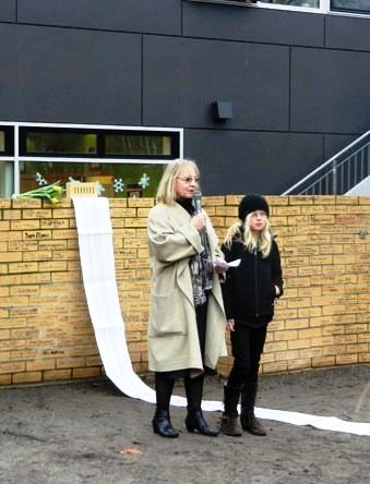 Schuldirektorin Christa Niclasen und die damalige Schülervertreterin Lilly sprechen 2012 anlässlich der Feierstunde auf dem Schulhof der Löcknitz-Grundschule in Berlin. Im Hintergrund steht die Mauer, die Schülerinnen und Schüler aus Gedenksteinen errichtet haben.