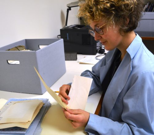 Sophia Stolf places the papers in folders, noting the type of document, and packs them in archival boxes.